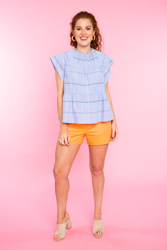 woman wearing orange shorts with plaid top