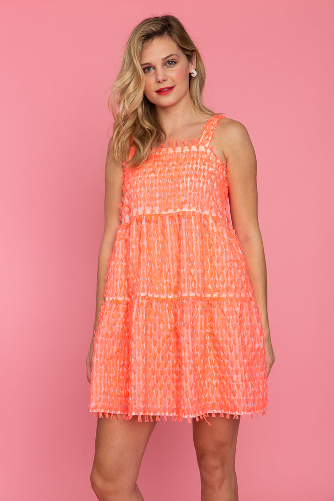 Woman in fringed coral tiered mini dress