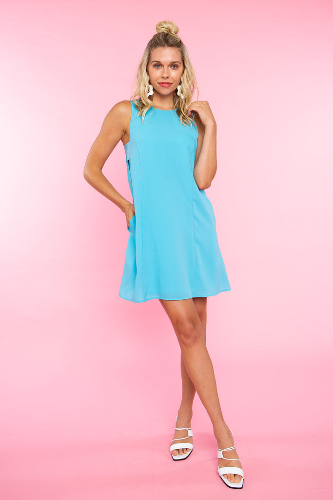 woman wearing short blue sleeveless dress with cut outs.