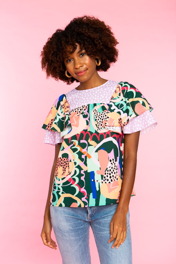 black woman wearing ruffle sleeve top in lilac and jungle print mix