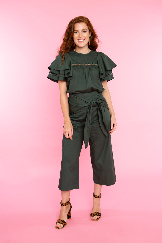 woman wearing cropped wide leg pants with tie at waist in green cotton