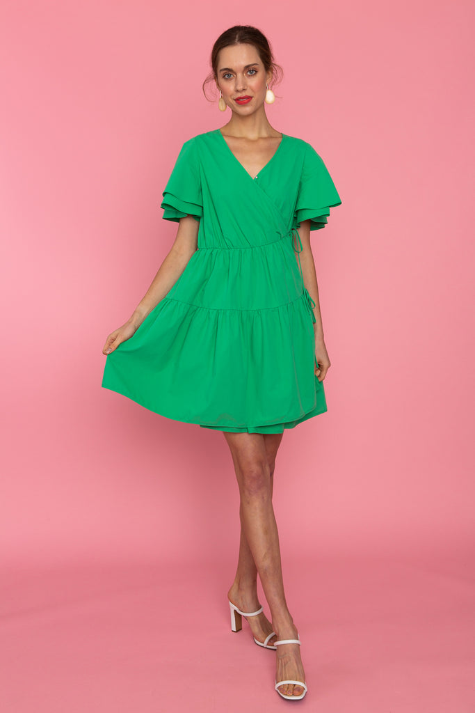 Woman in v neck green tiered dress with ties