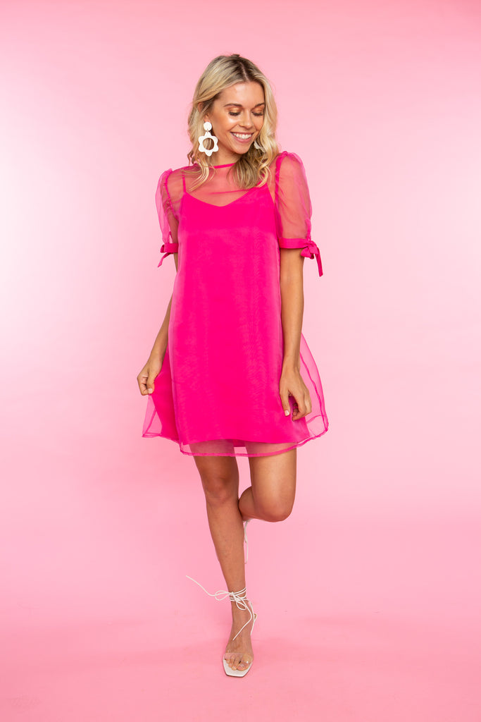 woman wearing short pink dress with sheer overlay and short sleeves