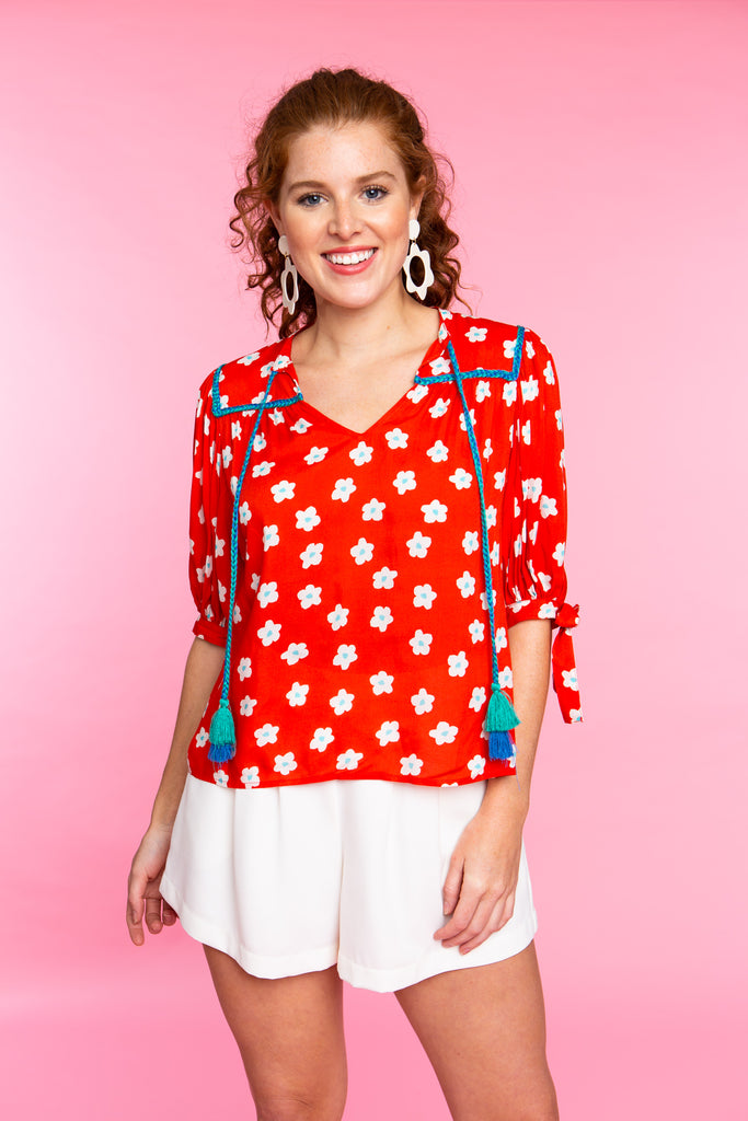 woman wearing red and white floral short sleeve top with tassels