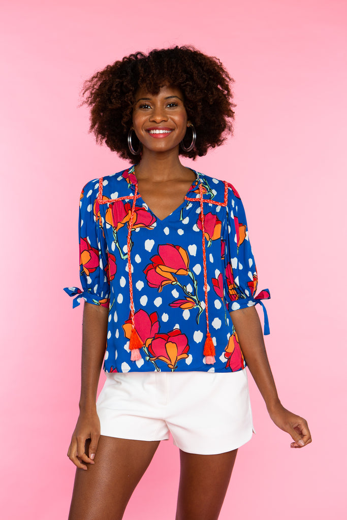 woman wearing blue floral print short sleeve shirt with pink tassels