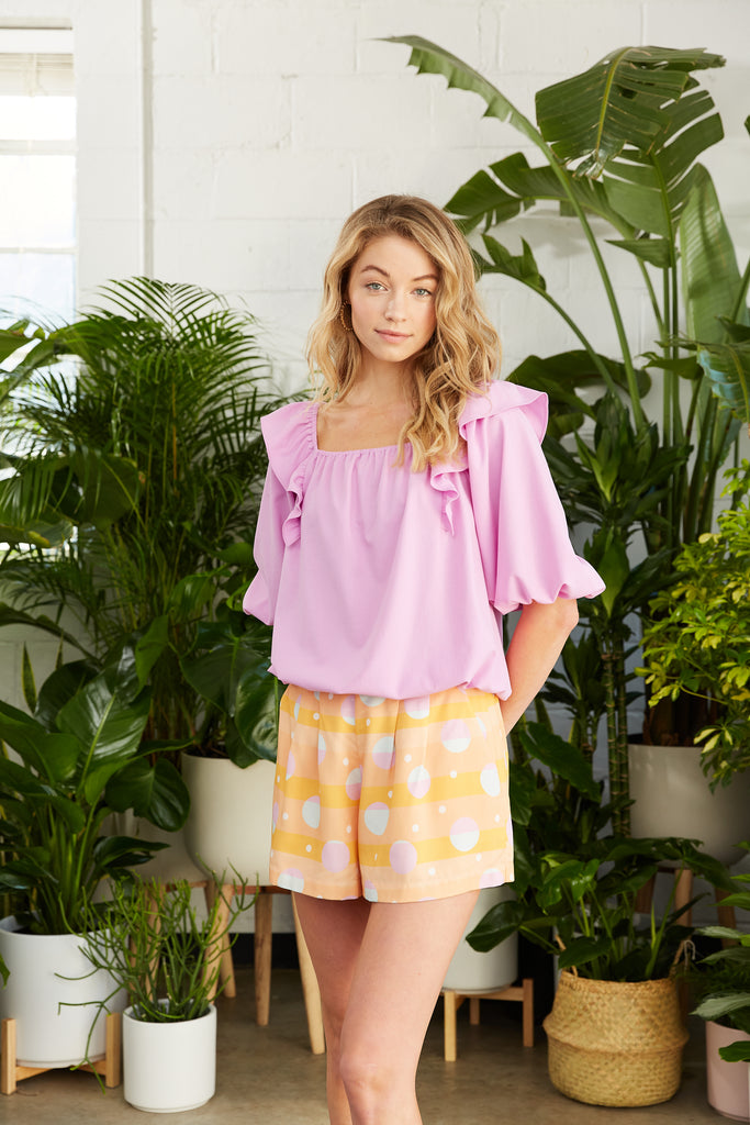 Blousy light purple top with printed orange shorts