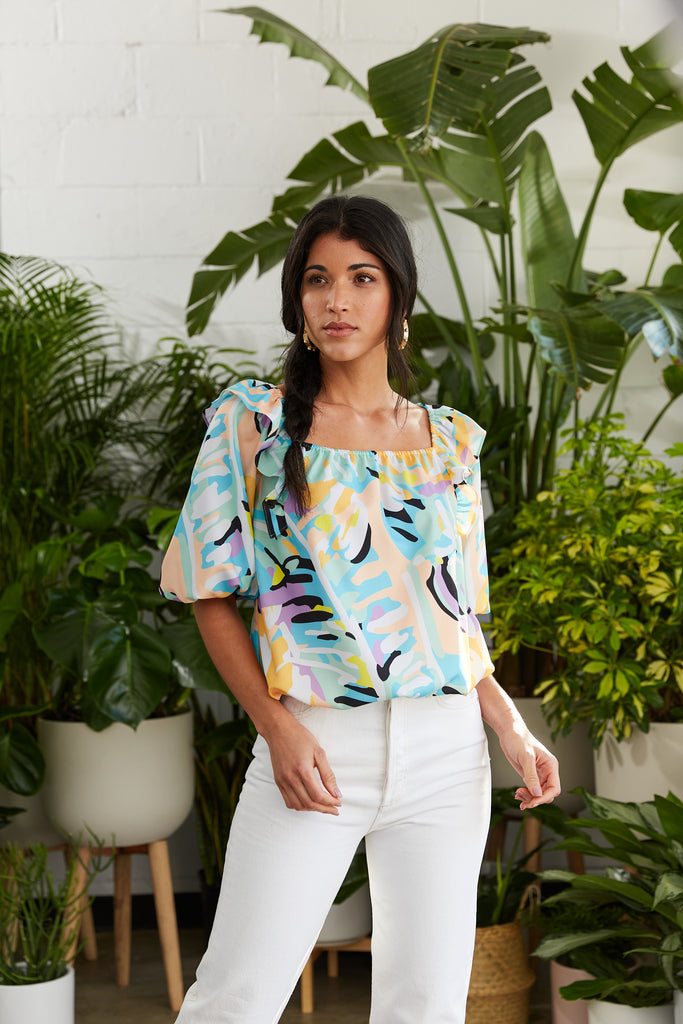 Blousy bright tropical printed top with ruffle at neckline and elasticized cuff and hem