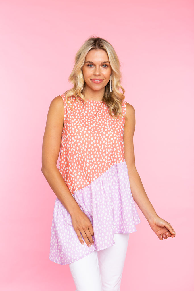 woman wearing peach and lilac print tank top with hi low hem and large buttons up the back