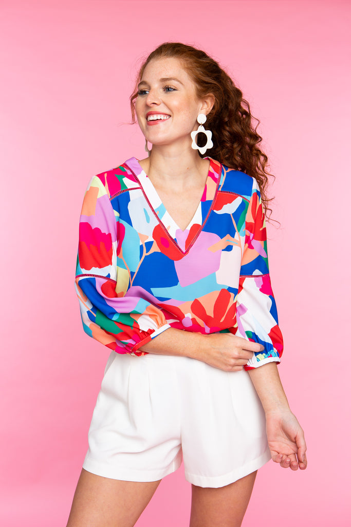 woman wearing colorful floral v neck shirt with white shorts