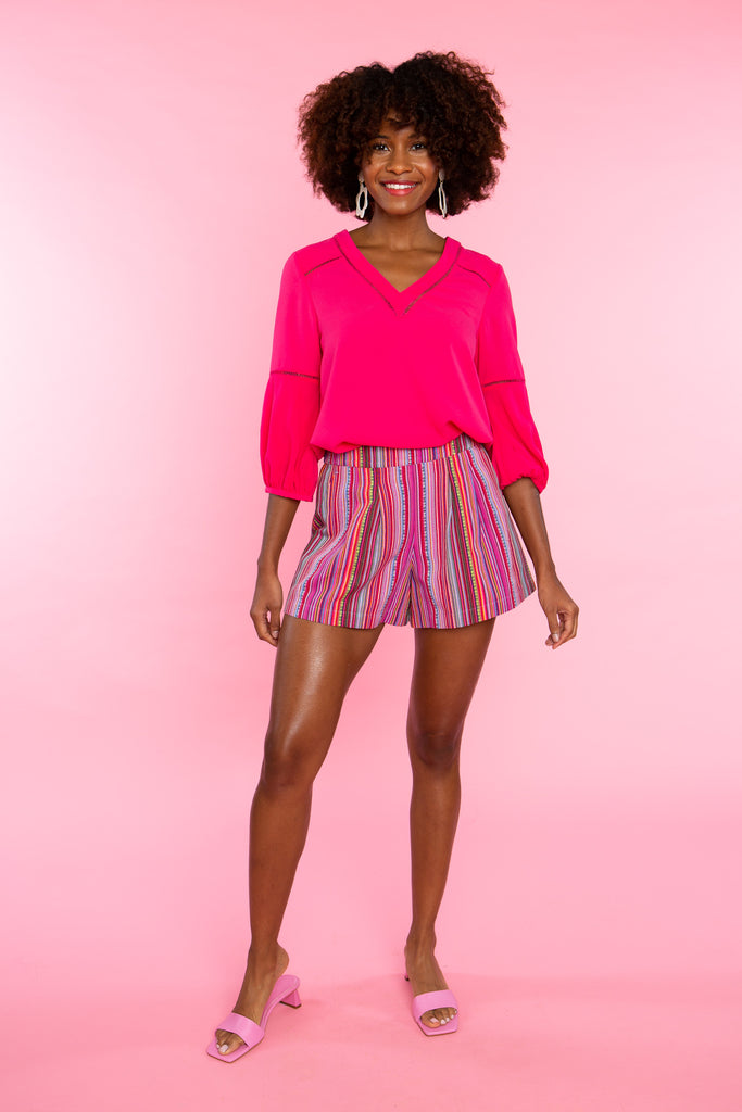 black woman wearing solid pink v neck shirt with pink stripe shorts