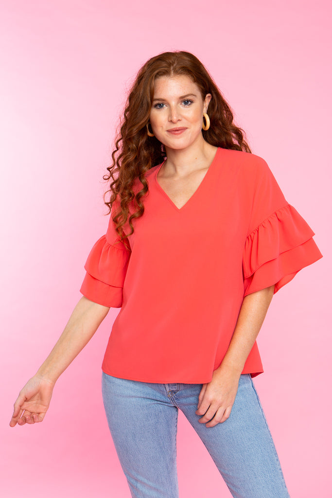 woman wearing coral v neck top with double ruffle sleeve