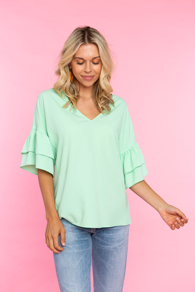 woman wearing mint v neck shirt with double ruffle sleeve