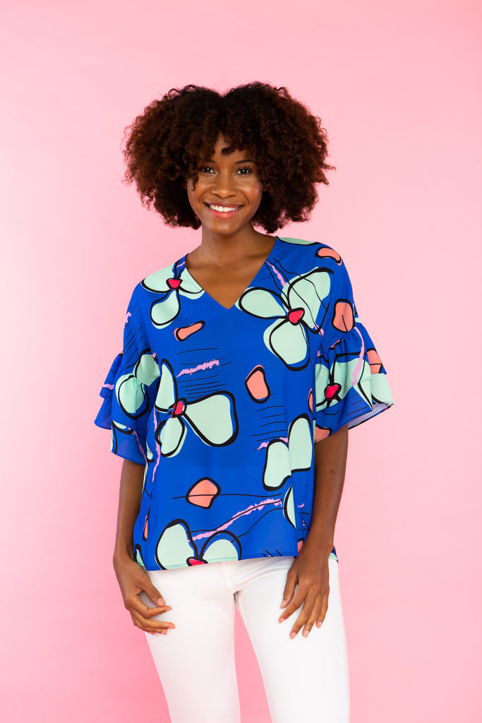 black woman wearing v neck blue shirt with abstract floral print and double ruffle sleeve