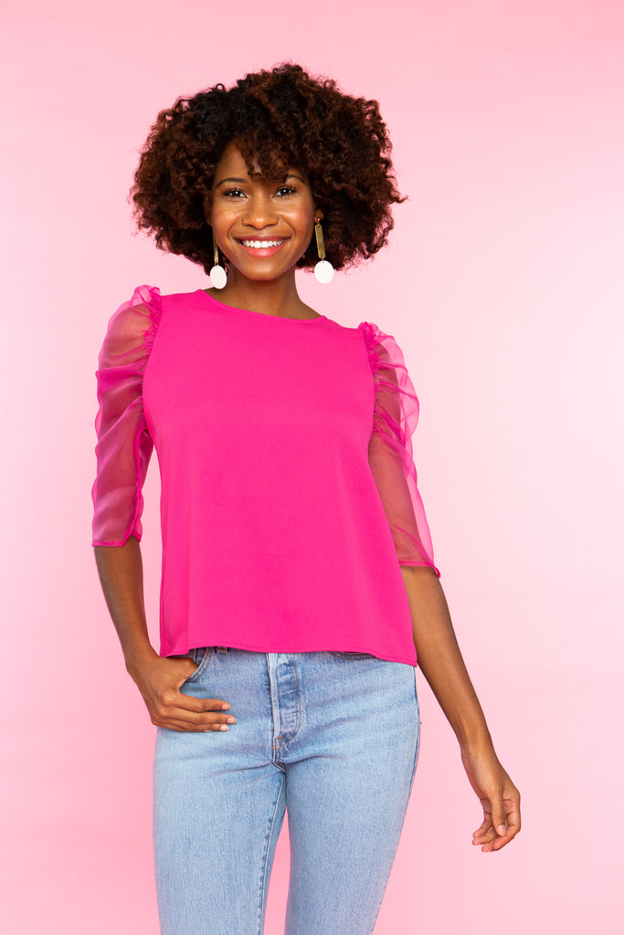 black woman wearing bright pink top with puffed sheer sleeve and jeans