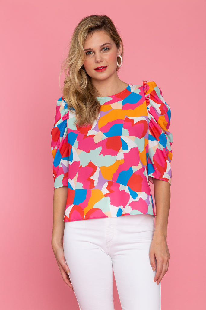 Woman in brightly colored puff sleeve top