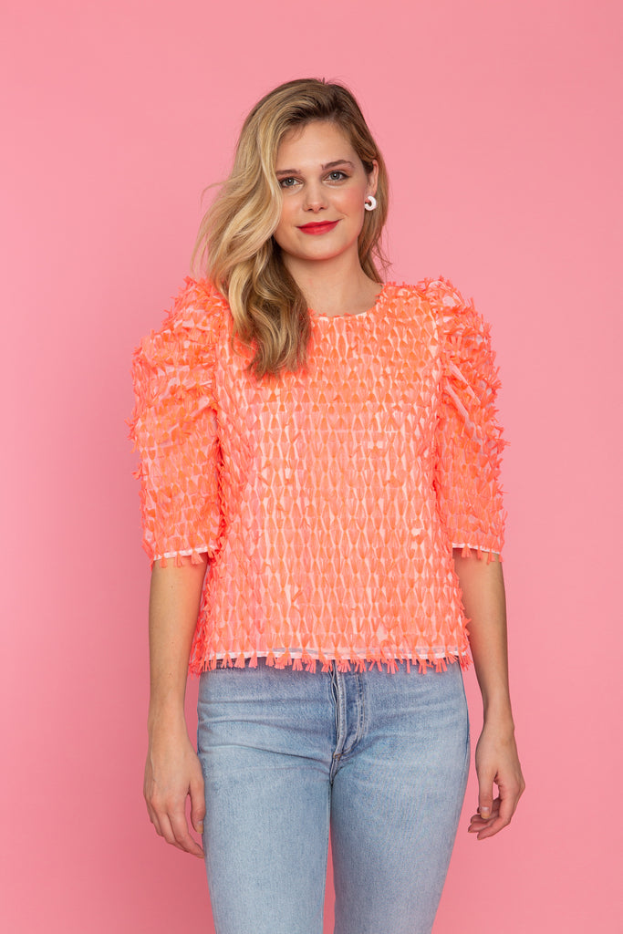 Woman wearing coral fringed top