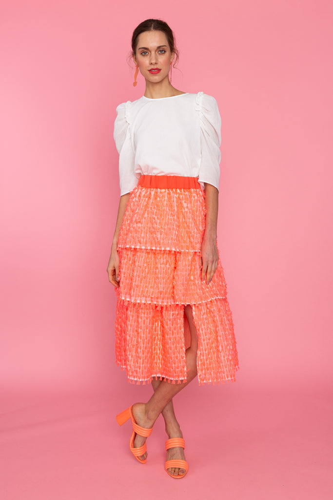 Woman in white puff sleeve top with coral fringed tiered skirt with slit