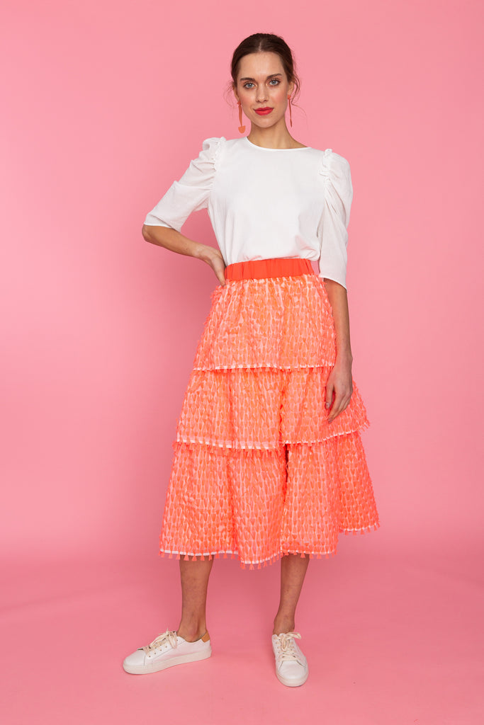 Woman in puff sleeve white top and coral tiered skirt