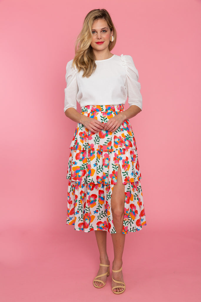Woman in puff sleeve white top and floral tiered midi skirt with slit
