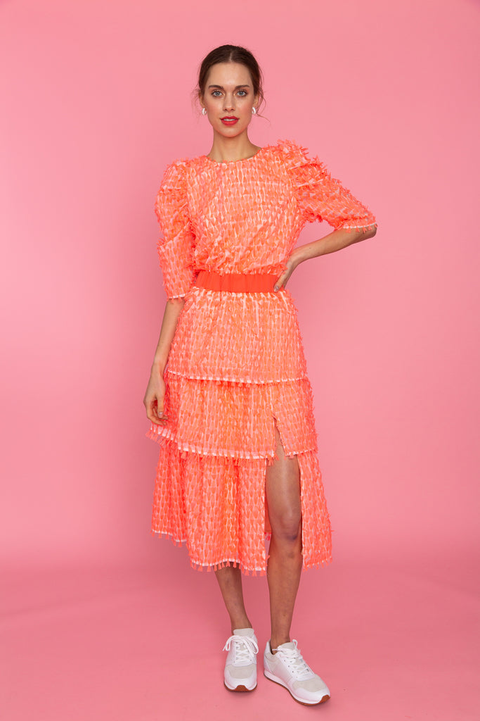 Woman in coral fringed puff sleeve top with matching skirt with slit
