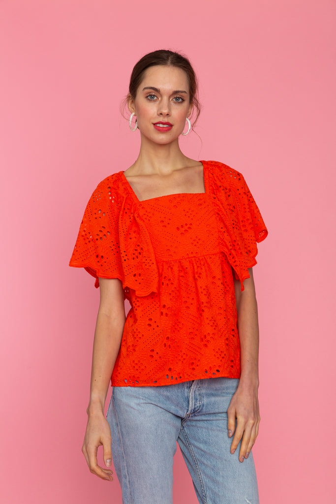 Woman in bright red eyelet blouse