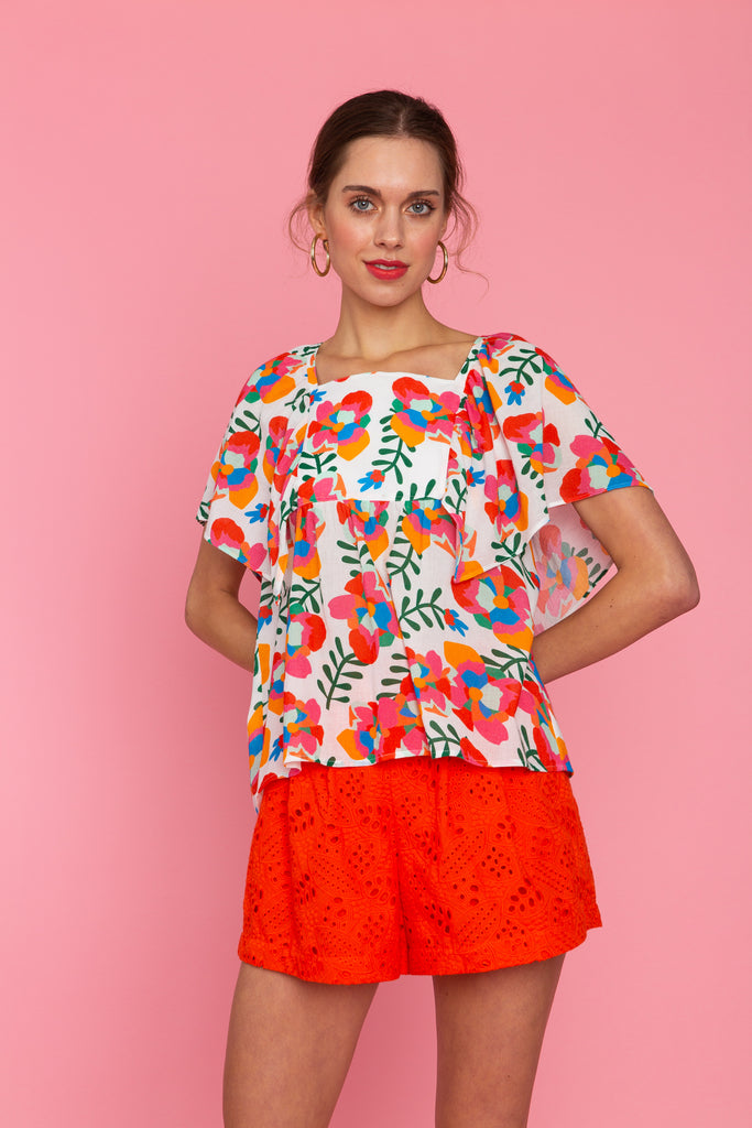 Woman in square neck floral top with red eyelet shorts