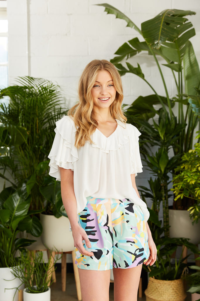 Flowy white top with flutter sleeve and ruffle at neckline and brightly colored shorts
