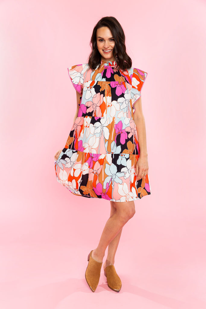 Woman in bright floral tiered mini dress