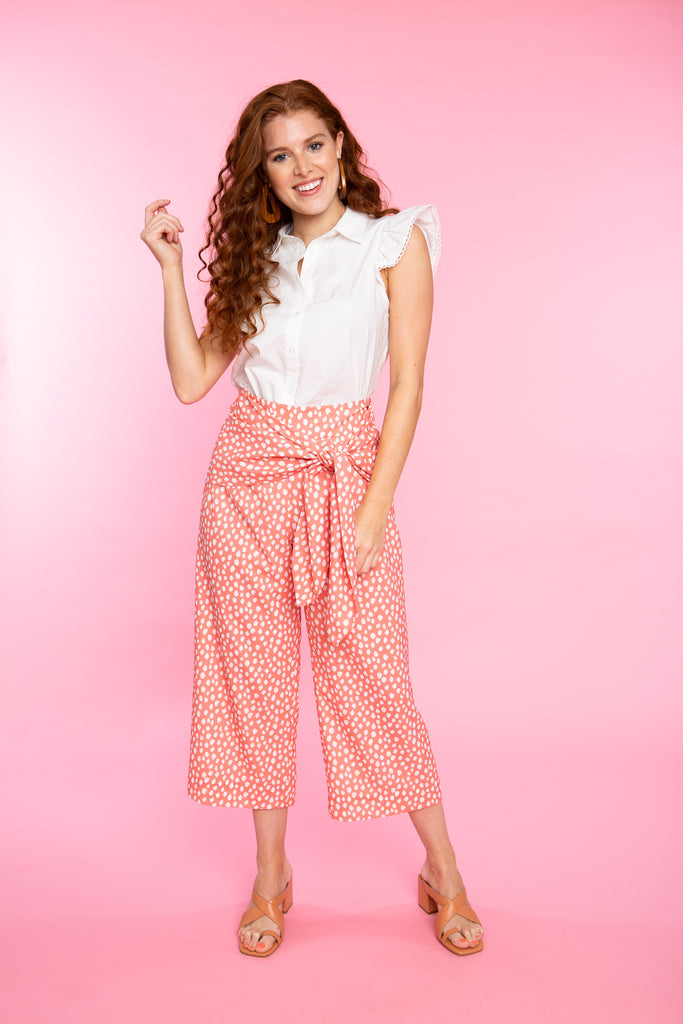 woman wearing cropped wide leg pant in peach print with a white sleeveless button down