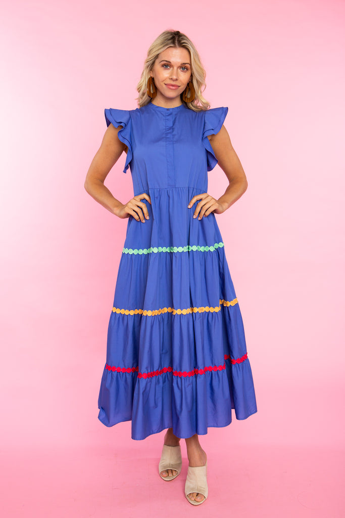 Woman wearing blue cotton maxi dress with colorful trim and ruffle sleeve