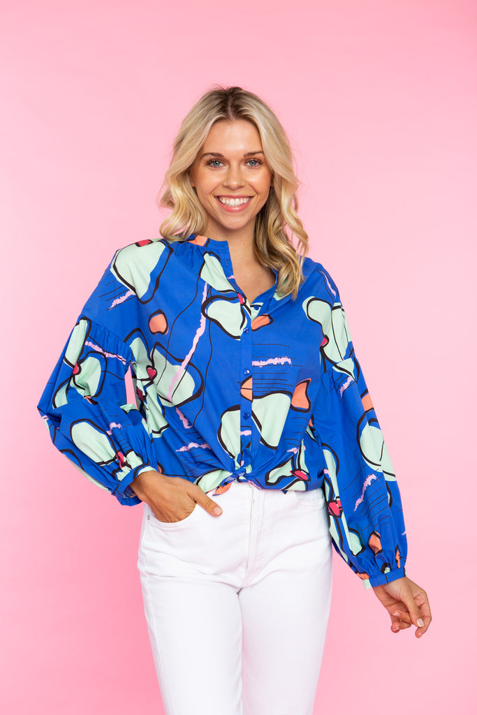 woman wearing collarless buttondown shirt with a balloon sleeve in blue orchid print