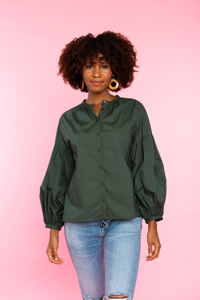 woman wearing collarless buttondown shirt with a balloon sleeve in green cotton