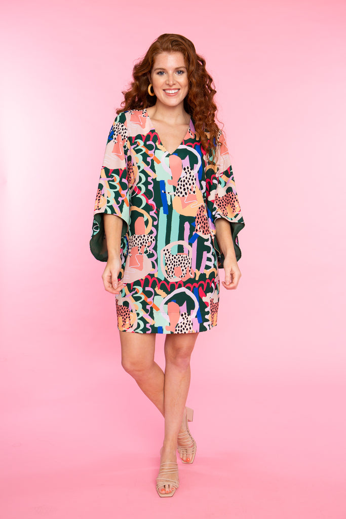 woman wearing jungle print v neck dress with flowy sleeve