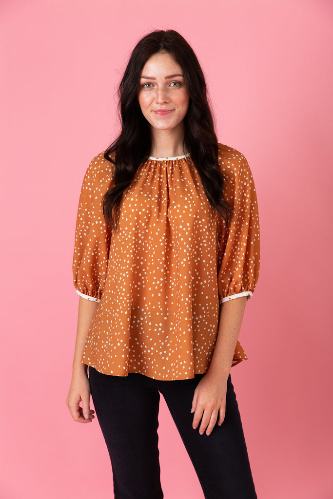 Woman in orange polka-dot shirt