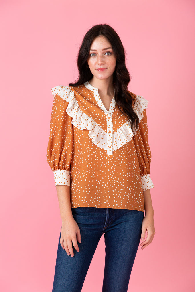 Woman in orange polka-dot blouse with contrasting ruffle