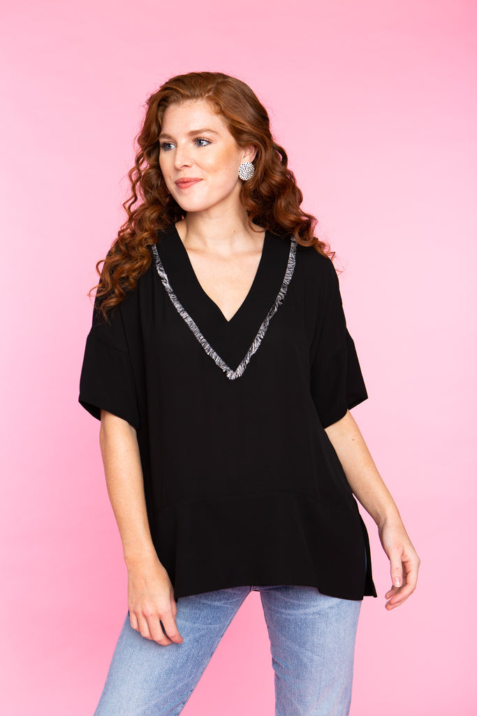 woman wearing short sleeve v neck tunic in black with fringe