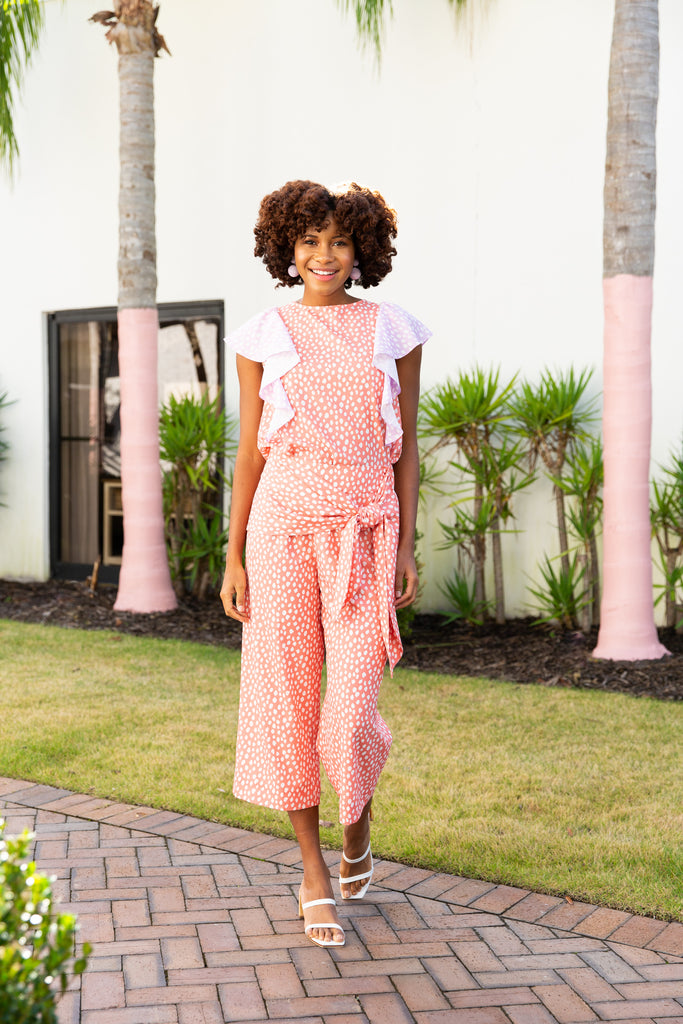woman wearing cropped wide leg pant in peach print with matching tank and contract ruffle