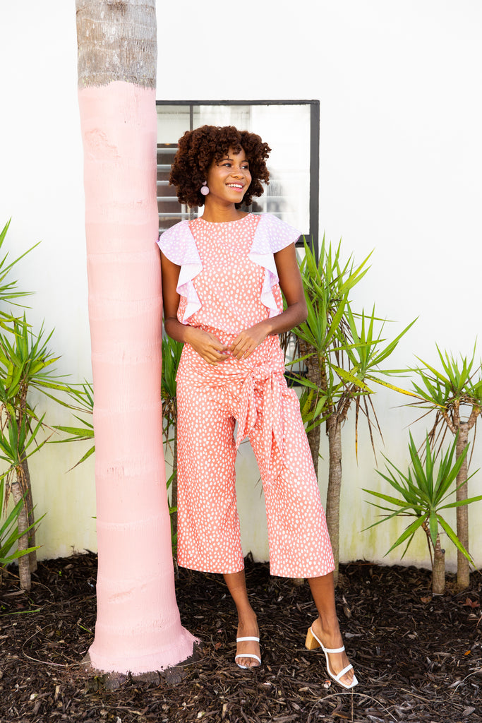 black woman wearing peach and lilac print mix tank with matching crop pants