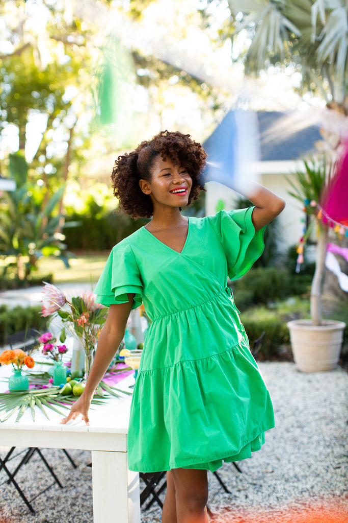 Black woman in v neck green tiered dress with flutter sleeve