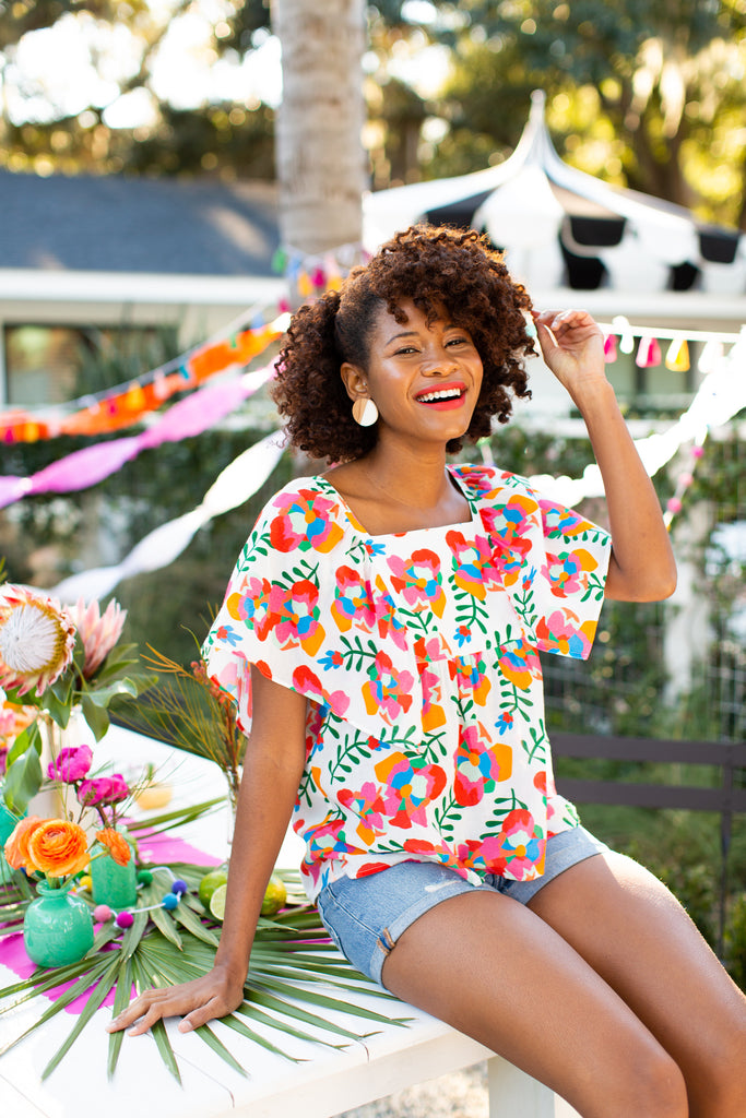 Black woman in square neck floral top