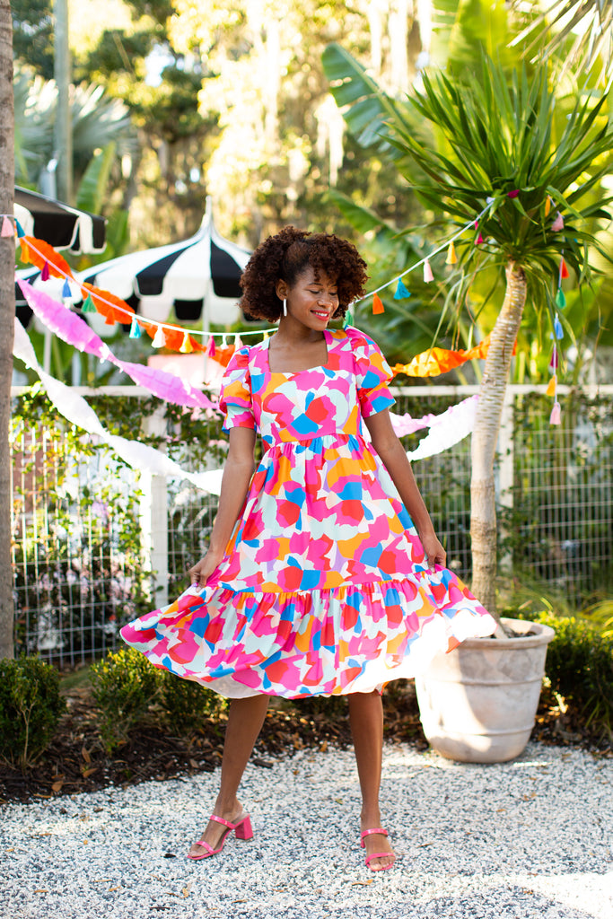 Black woman in brightly colored midi dress with puff sleeve