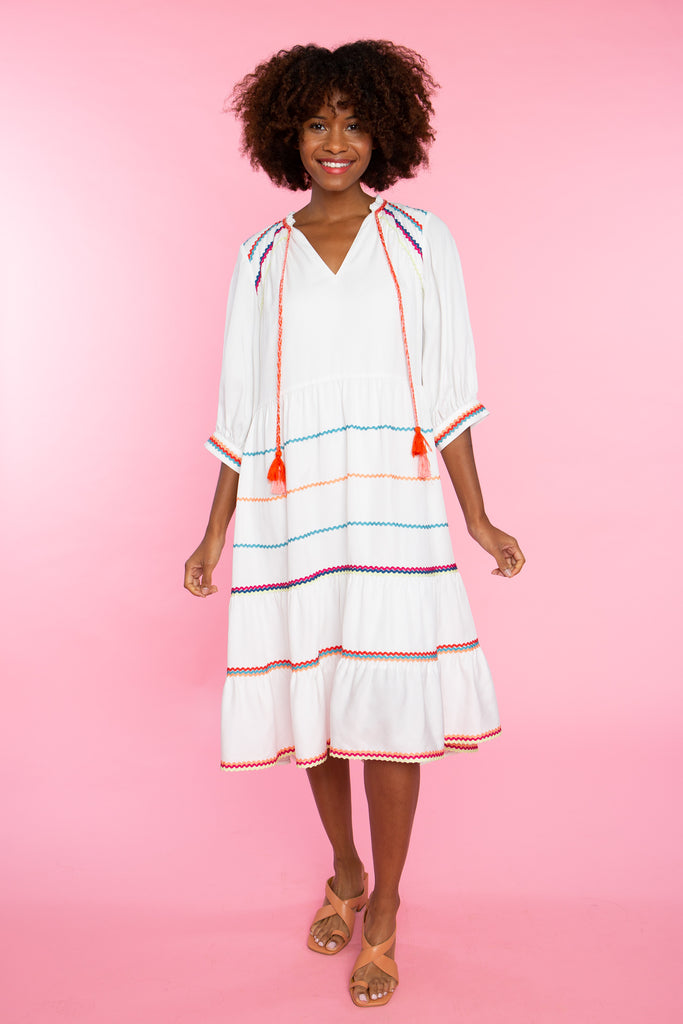black woman wearing white midi dress with colorful trim