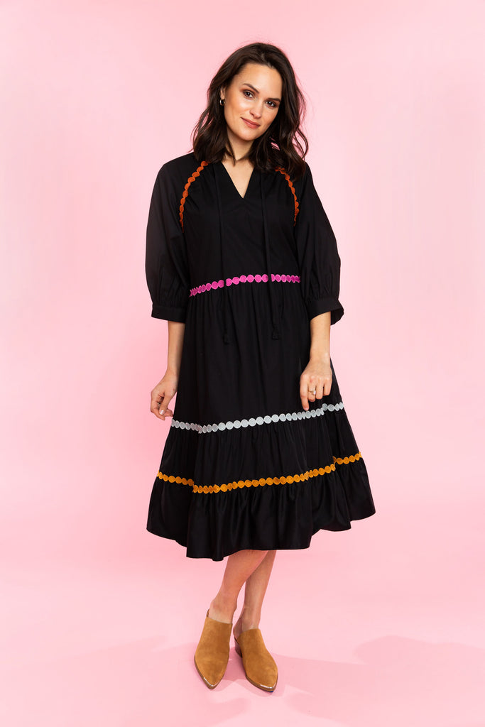 Woman in black tiered midi dress with colorful trim
