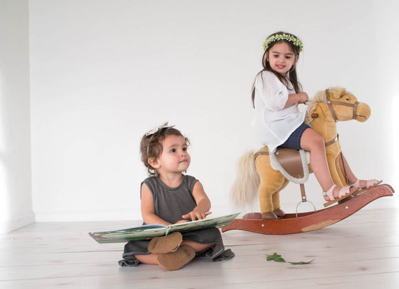 Two little girls, playing in a playroom wearing the Shiloh Z Spring Collection.
