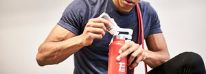 image of man squeezing electrolytes into a water bottle