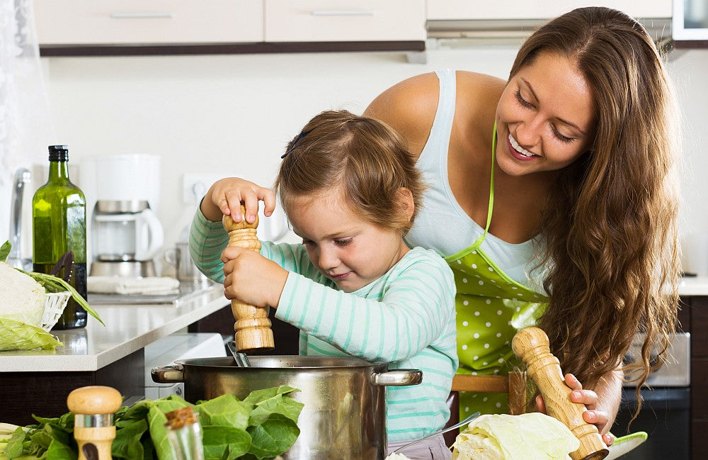 mom cooking with daughter showing good nutrition representing Bambinos Baby Food frozen meals and snacks for baby and toddlers