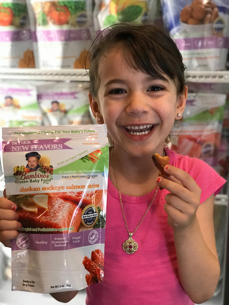 Alaskan Sockeye Salmon Strip for teething baby toddler snack finger food omega rich best product Bambinos baby food Zoi Maroudas healthy food product natural non gmo home delivery family business smiling cute girl boy eating fish
