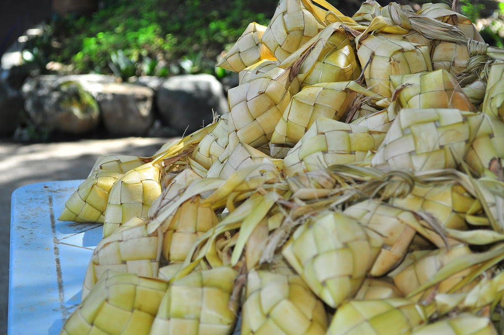 A large pile of puso, rice wrapped in woven palm leaves, to make religious offerings in the Philippines.
