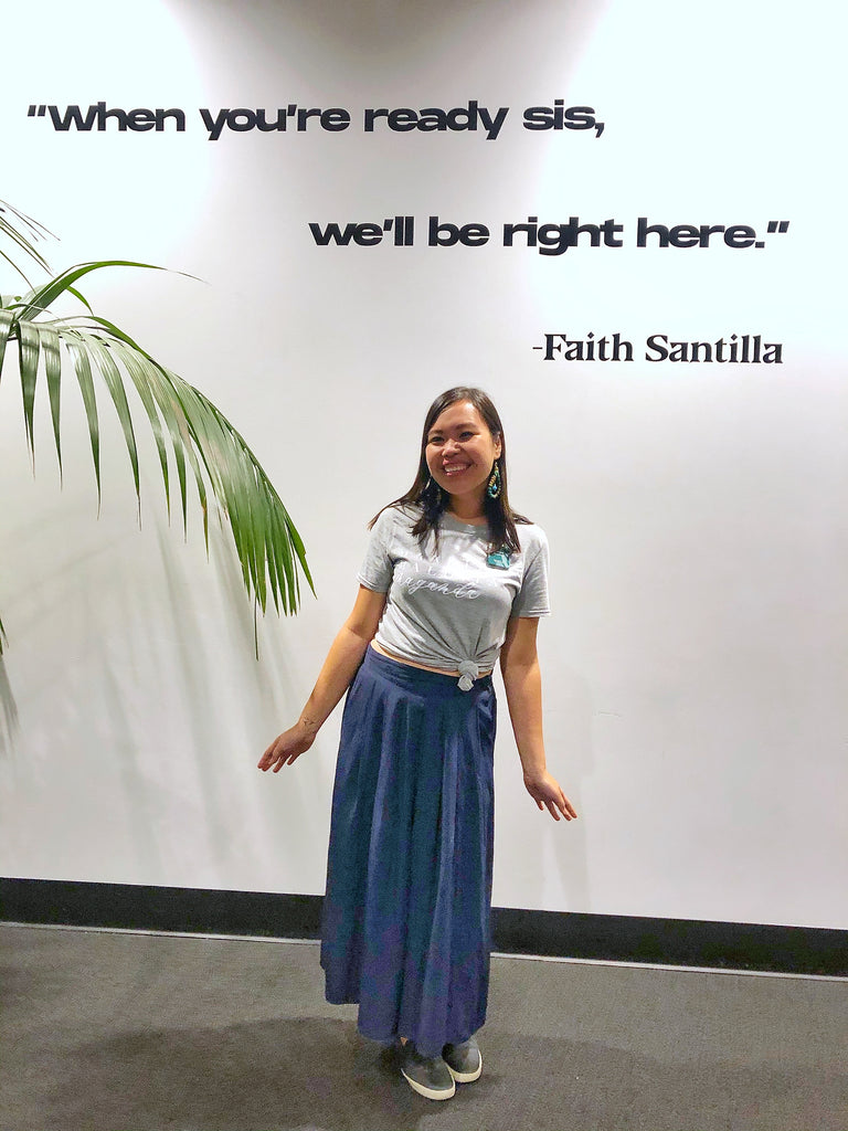 Gelaine Santiago, Social Entrepreneur and Co-Founder of Cambio & Co., standing beneath a sign that says 'when you're ready sis, we'll be right here' by Faith Santilla, at the Entrepinays Summit 2019 in San Francisco