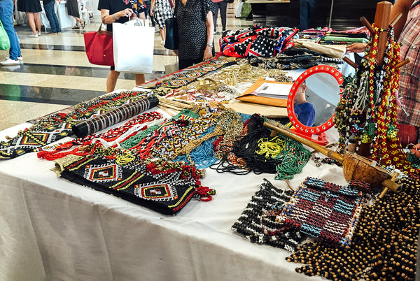 Colorful handmade woven bags, necklaces, bracelets, and belts